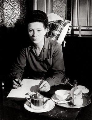 La escritora Simone de Beauvoir escribiendo mientras toma café