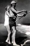 Arthur Miller pescando mientras Marilyn Monroe lo abraza