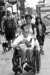 Hombre en silla leyendo mientras lo pasean por las calles de Nueva York
