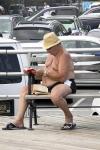 Un hombre sin camisa en el paseo marítimo de Brighton Beach lee dos libros.