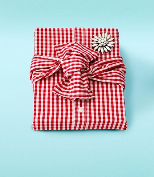 Libro de regalo envuelto con una camisa y un broche