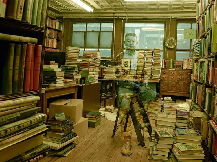 Liu Bolin camuflado entre libros y fotografiado por Annie Leibovitz